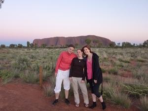 Drei Frauen stehen vor dem Ayers Rock