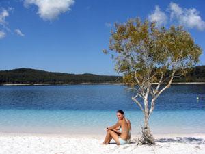 Frau sitzt am weißen Strand