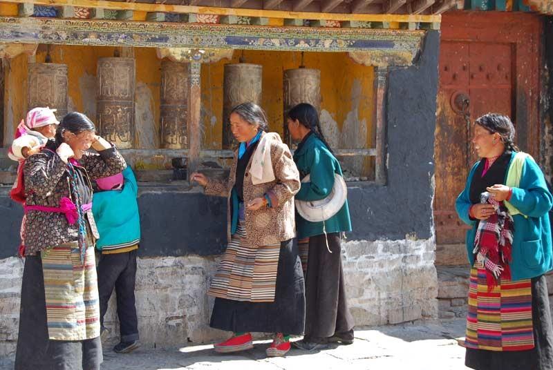 Tibetaanse vrouwen bij een gebedsmolen