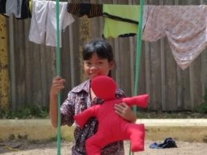 Kinde-auf-Schaukel-mit-roter-erlebe-Puppe
