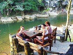 Familienreise Thailand: Reisende auf Terasse am Fluss des Khao Sok
