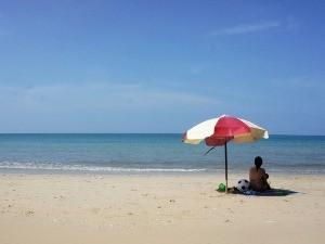 Kind unter Sonnenschirm am Strand von Koh Lanta