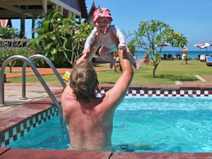 Vater mit Baby im Pool der Unterkunft auf Koh Lanta