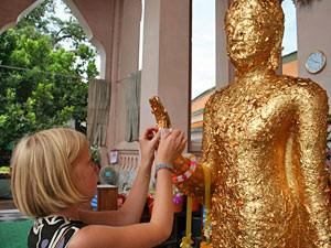 Mädchen beklebt Buddha mit Goldpapier