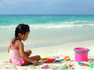 Familienreise Thailand: Mädchen baut Sandburgen am Strand