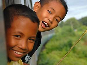 Zwei thailändische Kinder schauen aus dem Fenster der Burma Bahn