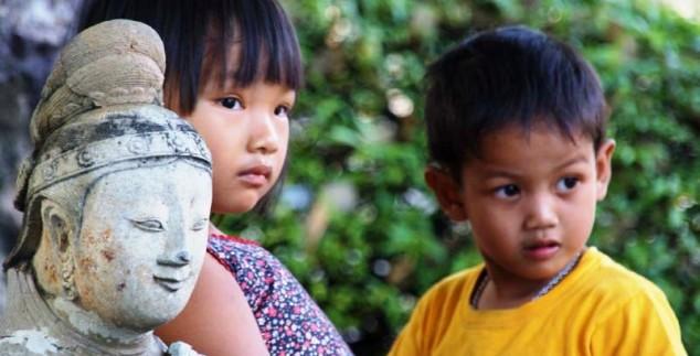 Zwei kleine thailändische Kinder vor einer Statue