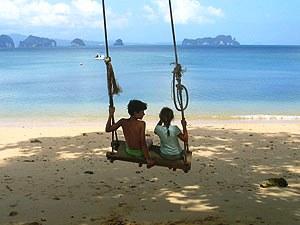 Kinder schaukeln am Strand auf Koh Lanta