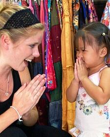 Begrüßung zwischen einer Reisenden und einem thailändischen Mädchen