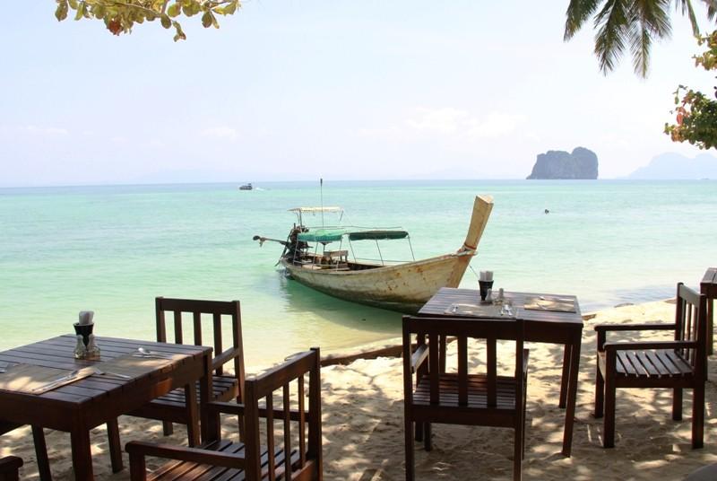 Restaurant am Meer mit Longtailboot im Hintergrund