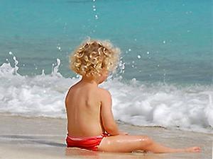 Kind sitzt im Sand am Meer