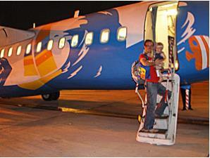 Familienreise Thailand: Vater mit Sohn vor dem Flugzeug
