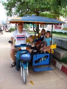 Vater spielt Chauffeur des Tuk Tuks in Bangkok