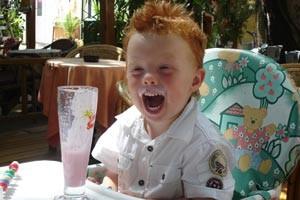 Ein Junge trinkt und lacht