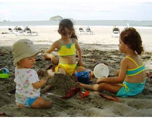 Kinder bauen am Strand eine Sandburg