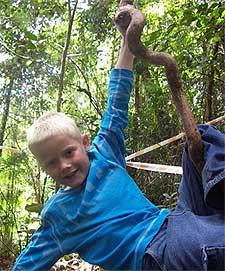 Junge schwingt an einer Liane