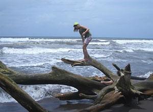 Mädchen steht auf einem Baumstamm am Meer