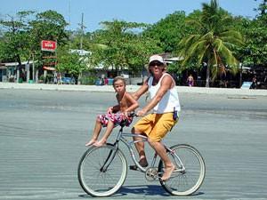 Vater mit Kind fährt Fahrrad am Sámara Beach