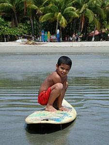 Ein Junge steht auf dem Surfbrett am Sámara Beach