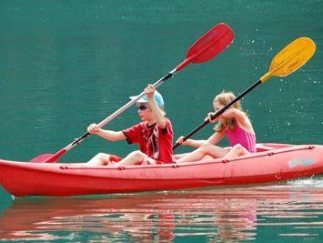 Zwei Kinder fahren Kanu