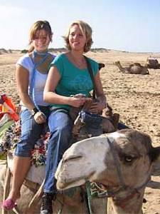 auf dem Rücken eines Kamels am Strand entlang
