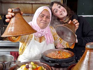 Reisende und Einheimische in der Küche vor einer dampfenden Tajine