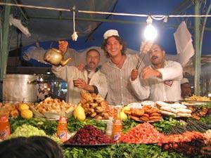 Drei Männer hinter einem Essensstand