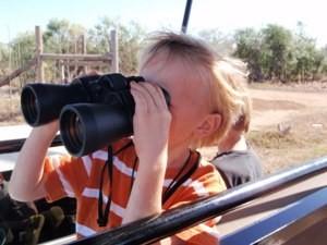 Südafrika Rundreise mit Kindern: Reisender Junge mit Fernglas auf Tierbeobachtung