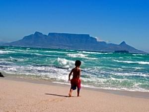 Garden Route mit Kindern: Junge am Strand mit Tafelberg im Hintergrund
