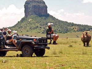 Ranger mit Reisenden auf Safari im Jeep