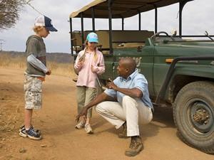 Ranger erklärt Reisenden im Entabeni Game Reserve die Spuren im Sand