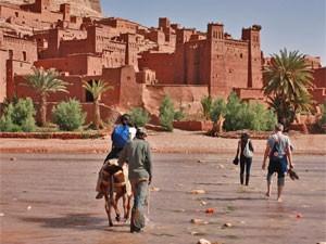Menschen die den Fluss vor der Kasbah überqueren
