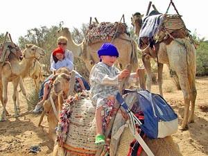 Marokko Rundreise: Kinder auf den Kamelen