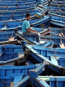 Essaouira: Blaue Fischebote auf dem ein Junge sitzt