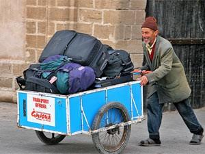 Voll beladener Gepäckkarren wird von einem älteren Mann geschoben