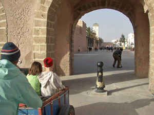 Kinder sitzen in der Handkarre des Kofferträgers und werden durch das Einganstor in Essaouira gefahren