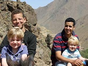Guides sitzen mit den Kindern auf dem Esel und reiten durch das Atlasgebirge