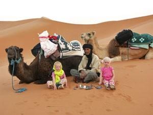 Kinder sitzen mit Beduinen vor den Kamelen
