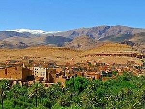 Aussicht über Palmenoase auf ein traditionelles Lehmdorf bei Ihrer Rundreise durch Marokko