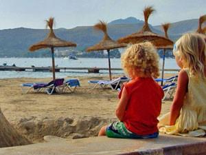 Essaouira: Zwei Kinder sitzen auf der Mauer am Strand und schauen zum Meer