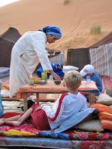 Kinder liegen auf den Matten vor dem Camp