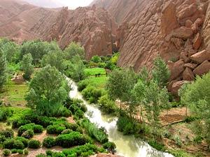 Dadestal - Grüne Schlucht mit Fluss umringt von roten Felsen