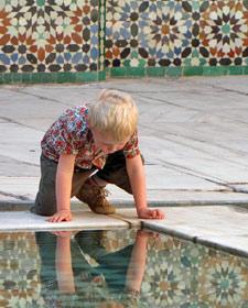 Kind erkennt sein Spiegelbild im Wasser des Brunnens