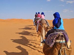 Kinder reiten auf dem Kamel durch die Wüste