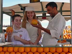 Verkäufer mit Kindern auf dem Orangenstand