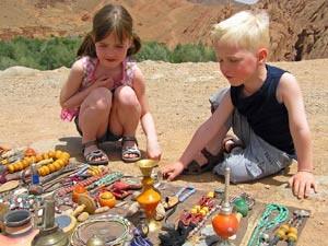 Zwei Kinder durchstöbern einen Souvenirstand bei der Rundreise durch Marokko