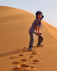Rundreise Marokko: Junge mit Turban ist auf der Sanddüne
