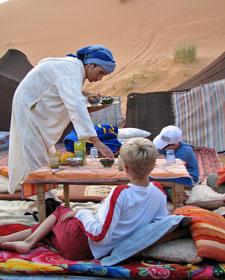 Rundreise Marokko: Junge liegt entspannt auf den Kissen im Sand