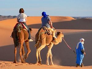Beduine mit zwei Kamelen und zwei Kindern darauf