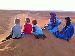 Zwei Beduinen sitzen mit drei Kindern auf der Wüstendüne